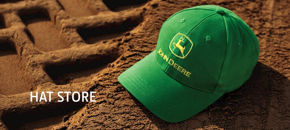 Green John Deere Hat Sitting On Freshly Tilled Soil