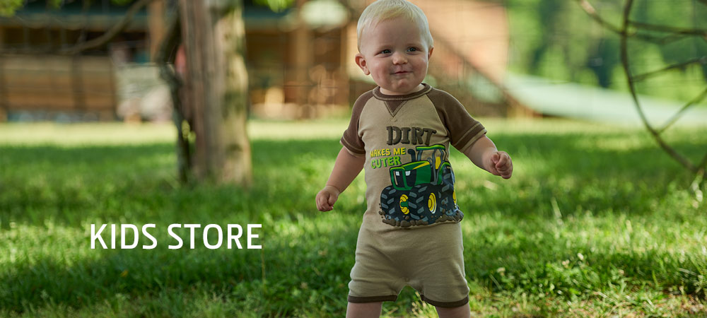 Infant standing on lawn in a John Deere Bodysuit