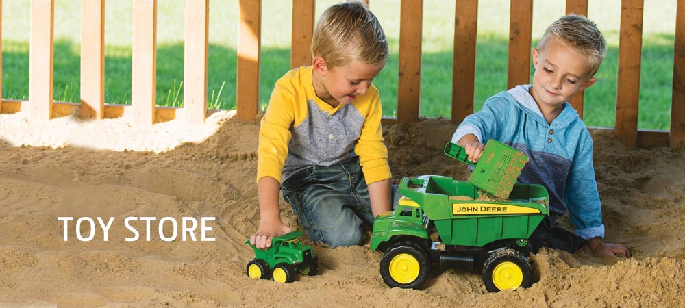 Two kids in a sand box playing with John Deere toy dump trucks